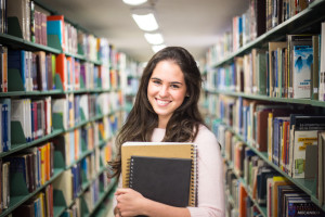 In the library - pretty female student with books working in a h